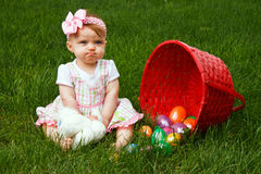 Baby Easter Eggs Frown. Baby girl frowning beside a spilled Easter egg basket Royalty Free Stock Image