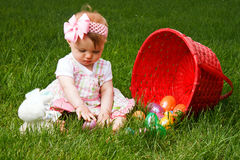Baby Easter Eggs Play. Baby playing with Easter eggs while sitting beside a spilled red basket Stock Photography