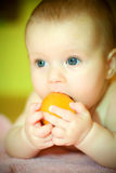 Baby eates tangerine Stock Photos