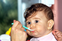 Baby eating. Meal with spoon Royalty Free Stock Photos