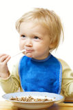 Baby eating. Little girl holding a spoon at her arms and eating a pap Royalty Free Stock Photo