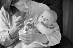 Baby Eating. Baby Boy being fed in his Mother's arms stock photo