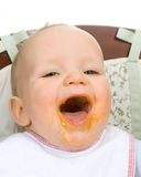 Baby eating. Happy baby with food all over the face Stock Photo