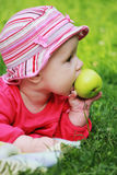 Baby is eating an apple Stock Images