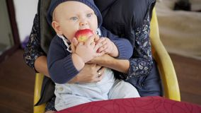 Baby is eating an apple on mother hands. Fruits background. stock video