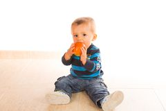 Baby eating apple. Sitting on the floor Royalty Free Stock Image