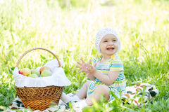 Baby eating apples outdoors Stock Photos