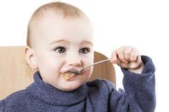 Baby eating applesauce. Studio shot isolated on white background Royalty Free Stock Photography