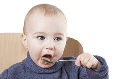 Baby eating applesauce. Studio shot isolated on white background Stock Photos