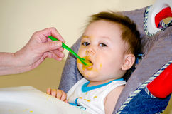 Baby eating baby food Stock Photography