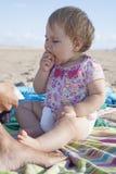 Baby eating banana at beach Royalty Free Stock Photos