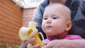 Baby eating banana from hands of mother stock footage