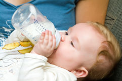 Baby eating from bottle. Portrait of a cute baby girl eating milk from bottle Royalty Free Stock Photo