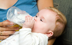 Baby eating from bottle. Portrait of a cute baby girl eating milk from bottle Royalty Free Stock Photography