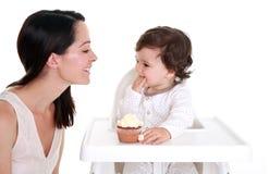 Baby eating cake with mum stock photo