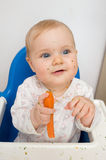 Baby eating carrot. S at home, all soiled vegetables, healthy nutrition of infants Stock Images