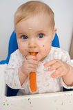 Baby eating carrot. S at home, all soiled vegetables, healthy nutrition of infants Stock Photography
