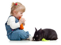Baby eating a carrot and feeding rabbit Stock Photography