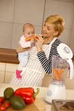 Baby eating carrot with mother Royalty Free Stock Photos