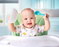 Baby eating,child`s nutrition. Baby eating at kitchen empty space table..Child`s nutrition stock image