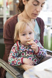 Baby eating chips on mother legs Royalty Free Stock Photo