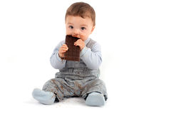 Baby eating chocolate. Adorable baby eating a plate of chocolate. Studio isolated on white background Stock Image