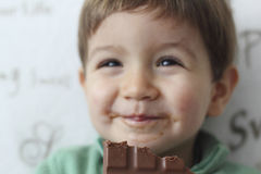 Baby eating a chocolate tablet Royalty Free Stock Images