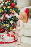Baby eating cookies near Christmas tree Royalty Free Stock Photos