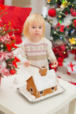 Baby eating cookies near Gingerbread house Stock Image