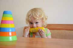 Baby eating corn. Beautiful little kid with blond hair and big blue eyes with appetite eats the boiled corn royalty free stock image