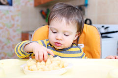 Baby eating corn curls Royalty Free Stock Images