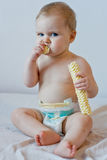 Baby eating crisps. At home dressed in a diaper royalty free stock photography
