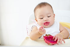 Baby eating dragon fruit Stock Photo