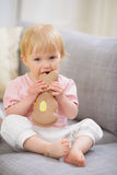 Baby eating Easter rabbit shaped cookie Stock Photo