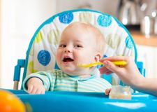Baby eating food on kitchen Stock Photo