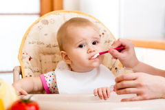 Baby eating food on kitchen. Baby girl eating food on kitchen stock image