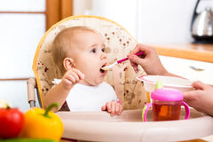 Baby eating food on kitchen Royalty Free Stock Photos