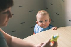 Baby eating food on kitchen. Mom is going to feed the child. Stock Photography