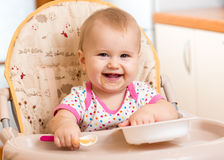 Baby eating food on kitchen. Smiling baby eating food on kitchen stock images
