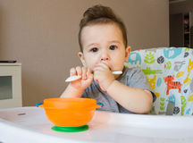 Baby eating food with a spoon, toddler eating messy and getting dirty, infant having oatmeal as breakfast Stock Photos