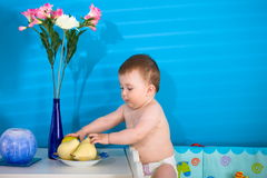 Baby eating fruits stock photos