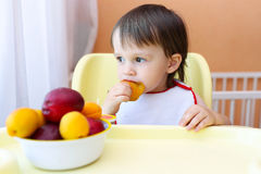 Baby eating fruits at home. 22 months baby eating peaches and apricotes Royalty Free Stock Photo