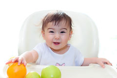 Baby eating fruits sit on the table stock photos