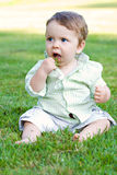Baby Eating Grass. A cute baby boy about to eat a handful of green grass that he just grabbed.  He was stopped just before succeeding Stock Image