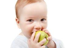 Baby eating green apple. stock photo