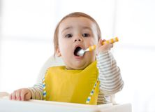 Baby eating healthy food with the left hand at home Stock Photos