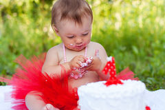 Baby eating her first birthday cake. Baby in red tutu eating her first birthday cake Stock Images