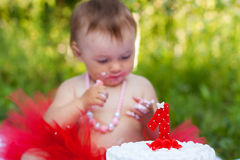 Baby eating her first birthday cake. Baby in red tutu eating her first birthday cake; focused on cake Stock Images