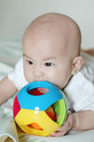Baby eating her toy Stock Images