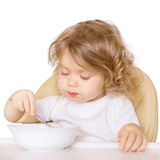 Baby eating in a high chair singly. Royalty Free Stock Photos